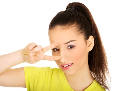 victory sign: Young student woman showing victory sign on eyes. Stock Photo