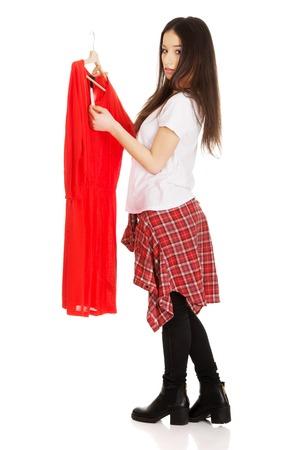 beautiful teen: Beautiful teen woman buying red dress. Stock Photo