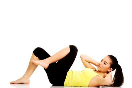 crunch: Woman exercising and doing a crunch to work her abs. Stock Photo