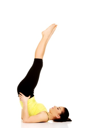 legs up: Fitness woman with her legs up practising yoga.
