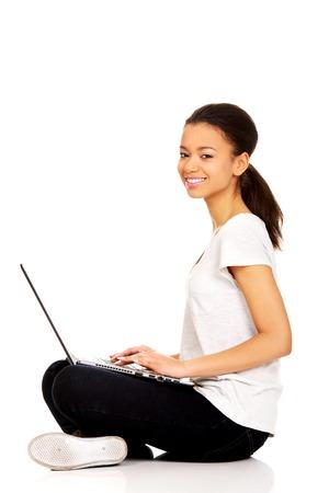 mujer sentada: Adolescente africano Cruz sentado de piernas con el portátil. Foto de archivo