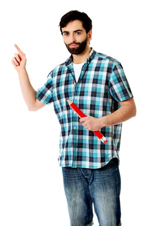 oversized: Young man holding oversized red pencil, pointing up. Stock Photo