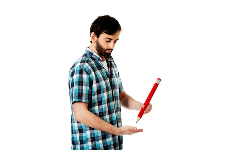 oversized: Young happy man writing with oversized red pencil.