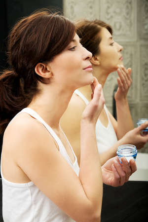 moisturize: Attractive woman putting anti-aging cream on her face.