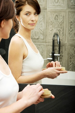 brush in: Woman cleaning nails with brush in bathroom. Stock Photo