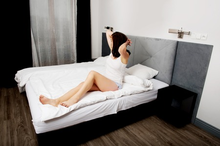 early 30s: Tired sleepy woman waking up and stretching in bedroom. Stock Photo