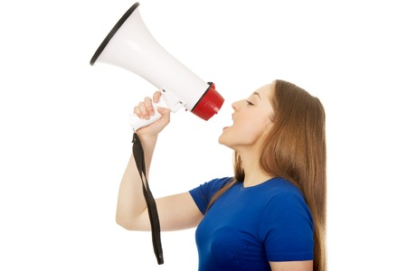 Screaming young teenage woman with megaphone. photo