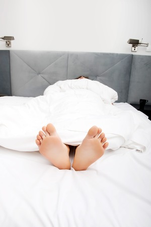 foots: Beautiful womans bare feet in bedroom. Stock Photo