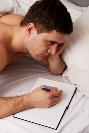 the weariness: Handsome man writing a note in his bedroom on bed.