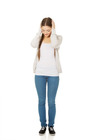 Tired teen woman covering ears with hands.