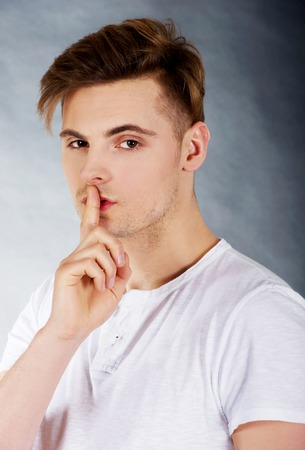 hushed: Young handsome man with finger on lips.