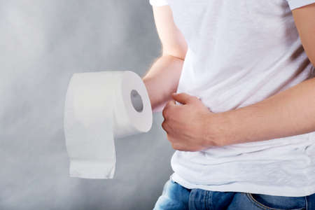 a toilet seat: Young man with stomach issues holding toilet paper.