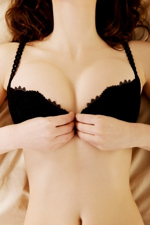 Sexy brunette woman taking off her bra on the bed.