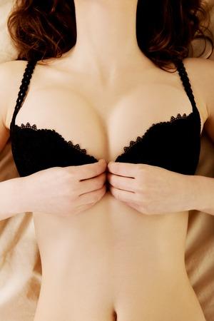 cuerpo perfecto femenino: Sexy morena mujer quit�ndose el sujetador en la cama.