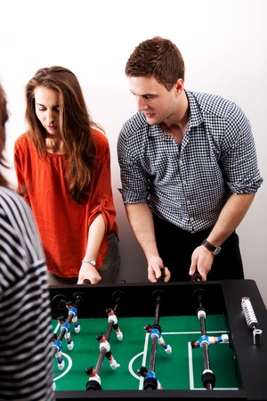 joyfull: Friends having fun together playing table football.