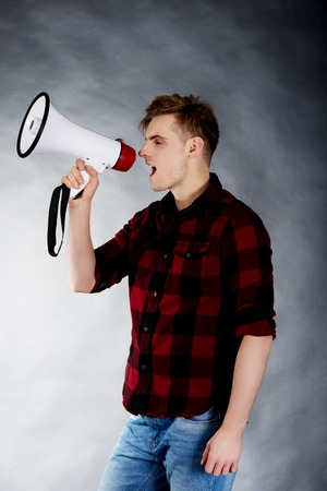annoucement: Young handsome man shouting in megaphone. Stock Photo
