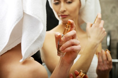 parfume: Attractive woman applying parfume in the bathroom. Stock Photo