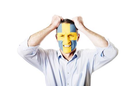 bandera de suecia: Hombre maduro con Suecia bandera pintada en la cara.