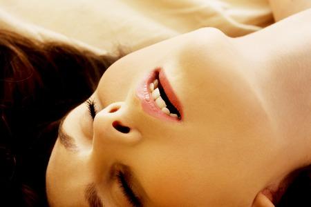 nude woman: Mujer joven en la cama conseguir el orgasmo. Foto de archivo