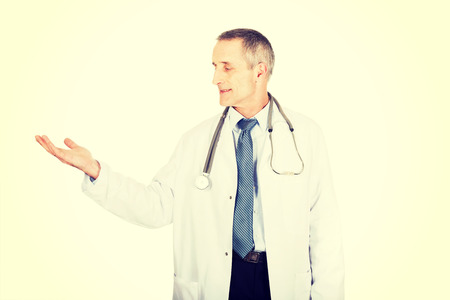 doctor holding gift: Mature male doctor holding copy space.