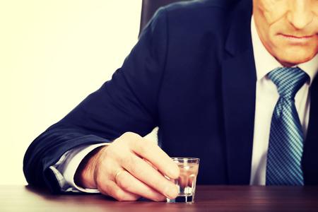 overworked: Overworked man drinking vodka in office. Stock Photo