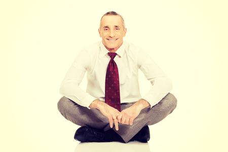 crosslegged: Happy businessman sitting cross-legged on the floor. Stock Photo