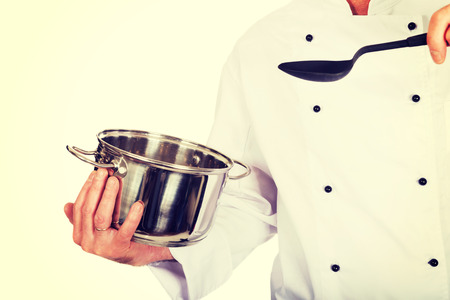 broth: Restaurant chefs hand holding steel pot and spoon