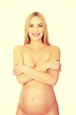 nude blonde woman: Well groomed pregnant woman covering her breast. Stock Photo