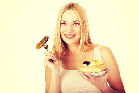 prickles: Pregnant woman eating prickles and cake Stock Photo
