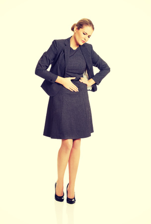 stomachache: Blonde businesswoman with strong stomachache. Stock Photo