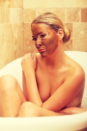 chocolate mask: Thoughtful woman sitting in a bath with chocolate mask on face.