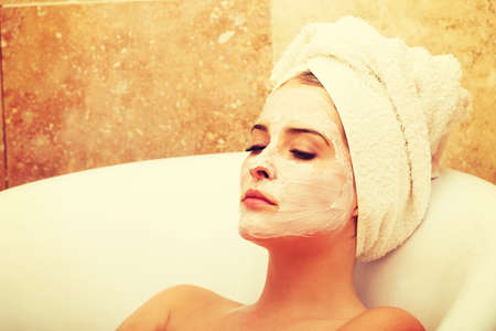 body mask: Relaxing woman with closed eyes and cream lotion on face