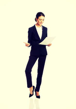 knee bend: Happy businesswoman with paper notes.