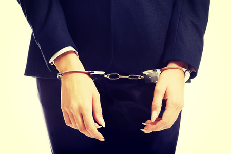 arrested: Arrested businesswoman hands with handcuffs. Stock Photo