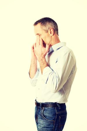 sinus: Mature man holding his nose because of sinus pain.