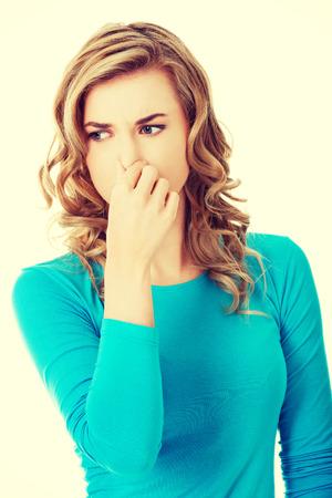 intolerable: Portrait of a woman clogging nose.