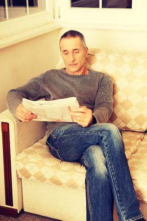 only one mid adult male: Mature man relaxing with newspaper on the sofa.