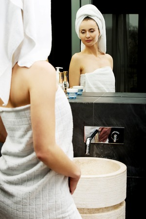 wrapped in a towel: Beautiful woman wrapped in towel at bathroom. Stock Photo