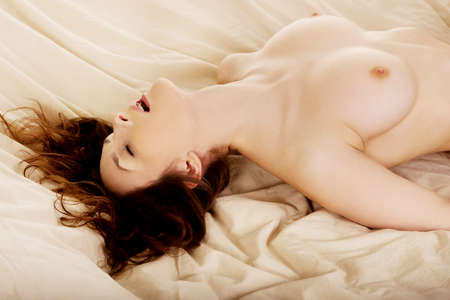 naked woman: Young naked woman in bed getting orgasm. Stock Photo