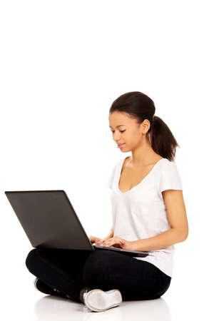 legged: African teen sitting cross legged with laptop.