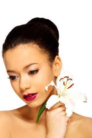womanliness: Beauty face of african woman with lily flower.