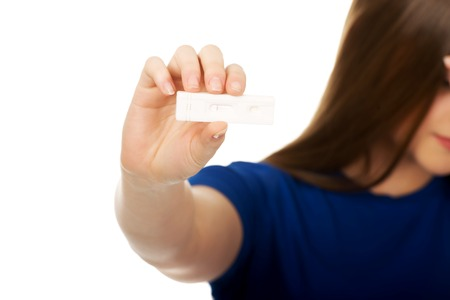 conceive: Unhappy teenage woman holding pregnancy test. Stock Photo