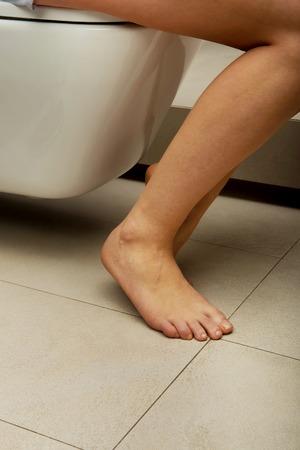 constipated: La mujer cauc�sica est� sentado en el inodoro.