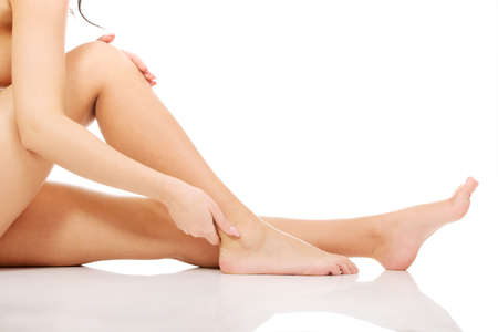 mujeres fitness: Mujer del balneario de tocar sus delgadas piernas.