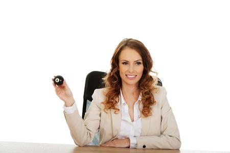 billard: Businesswoman holding eight billiard ball by a desk.