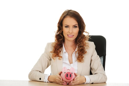 coinbank: Mujer de negocios con una hucha en un escritorio.