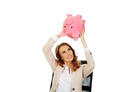 Business woman shaking a piggybank by a desk. photo