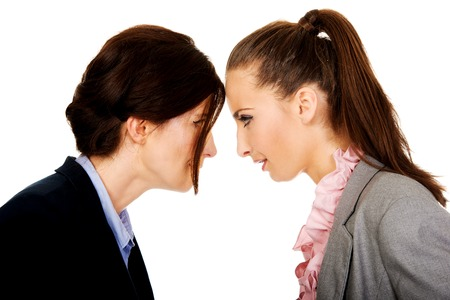 communication breakdown: Two angry businesswomans standing face to face.