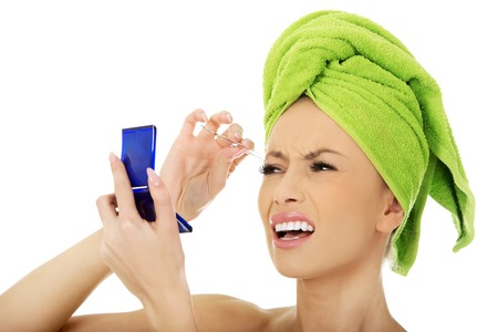 tweezing: Beautiful caucasian woman plucking her eyebrow.