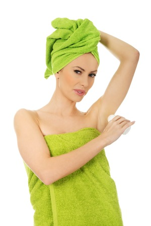 wrapped in a towel: Young woman wrapped in towel using deodorant.